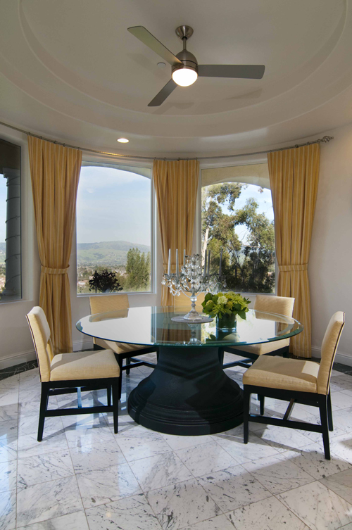 The breakfast nook facing the Eastern mountains, features a black cast  stone pedestal table and a clear glass top to accommodate 8 to 10.