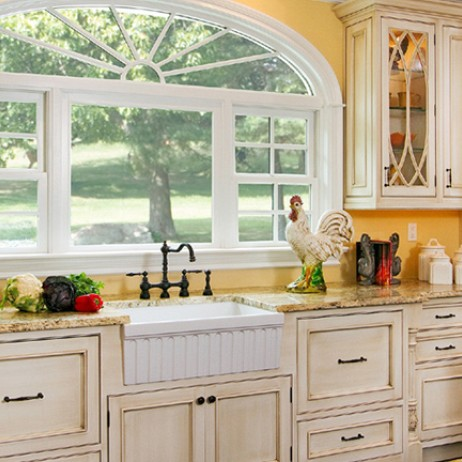 Cottage kitchen bathed in sunlight by Plain & Fancy Custom Cabinetry